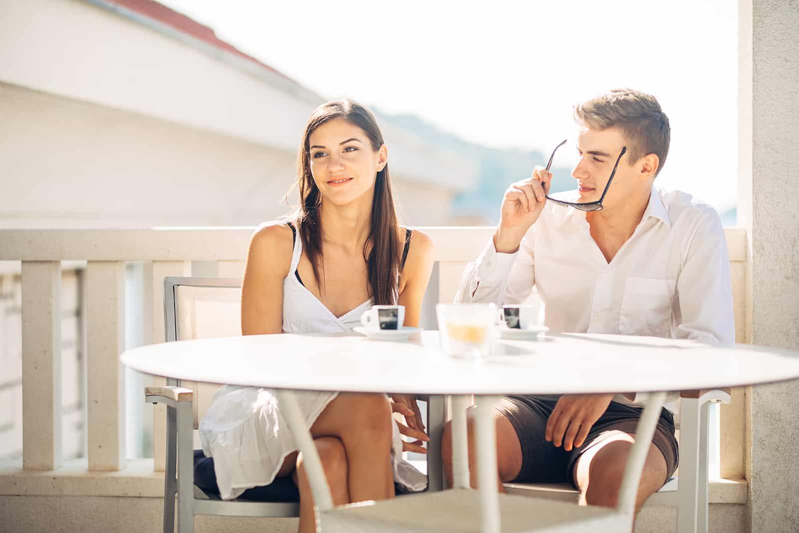 Ein Mann, der eine Frau ansieht, die mit ihm bei einem Date im Café sitzt