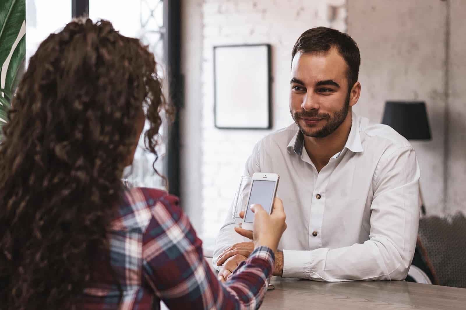ein Mann, der eine Frau mit ihrem Smartphone an einem Datum betrachtet