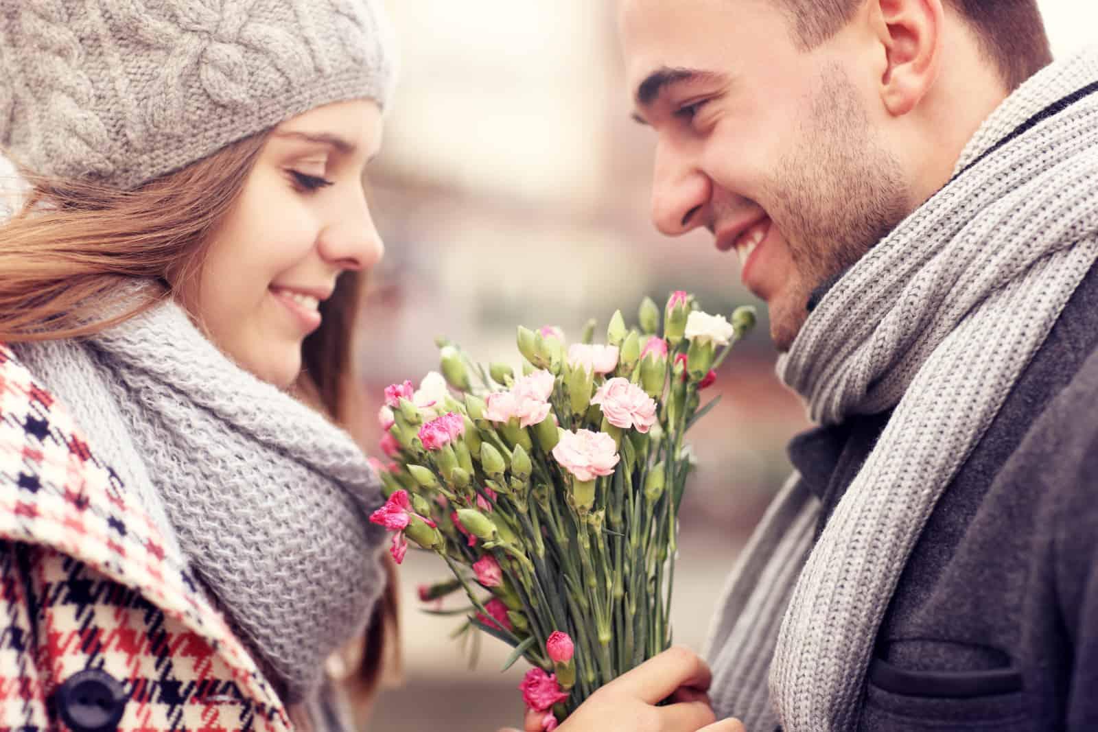 ein Mann, der einem Mädchen Blumen gibt