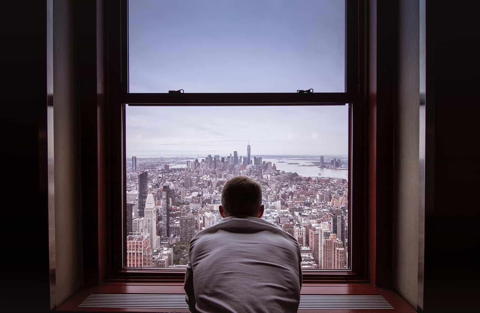 Ein Mann lehnte sich an das Fenster zur Stadt