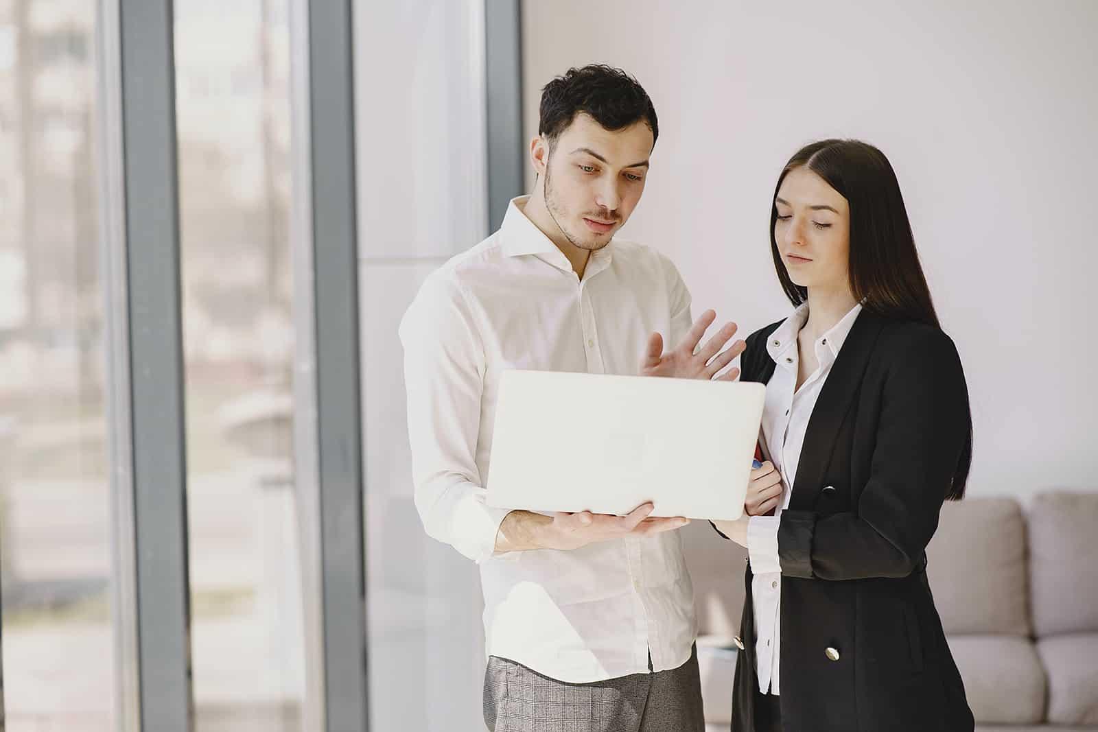 Ein Mann mit einem Laptop spricht mit einer Kollegin, während er nahe beieinander steht
