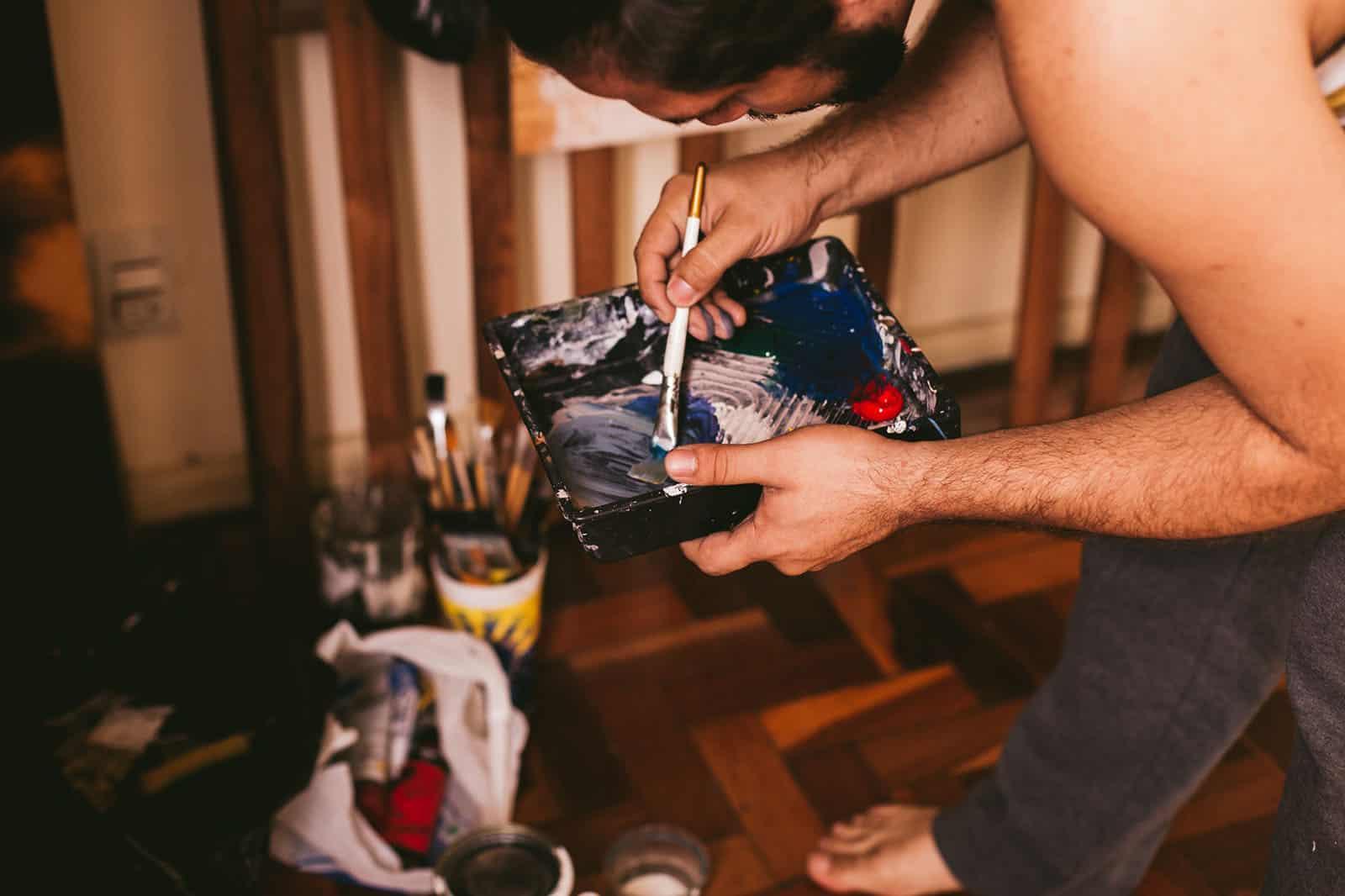 ein Mann, der beim Malen einen Pinsel hält