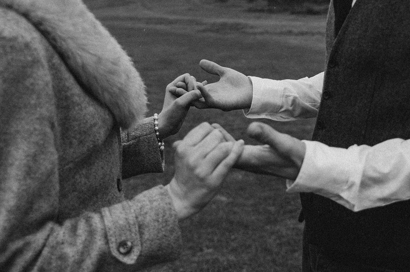 Ein Mann und eine Frau halten sich an den Händen, während sie nahe beieinander stehen