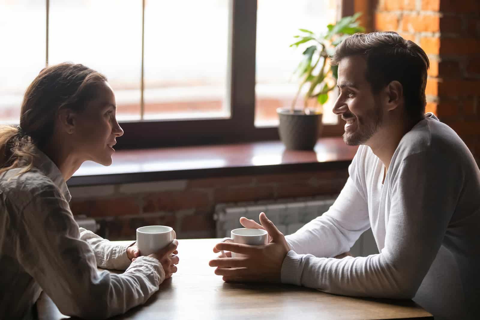 Ein Mann und eine Frau unterhalten sich, während sie in einem Café sitzen