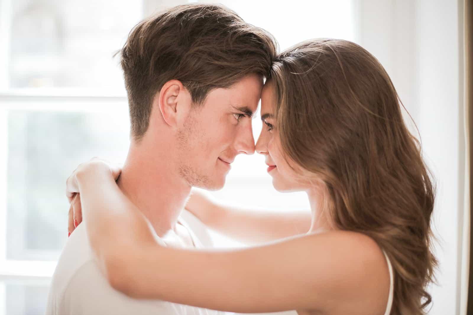 Ein Mann und eine Frau sehen sich beim Umarmen an