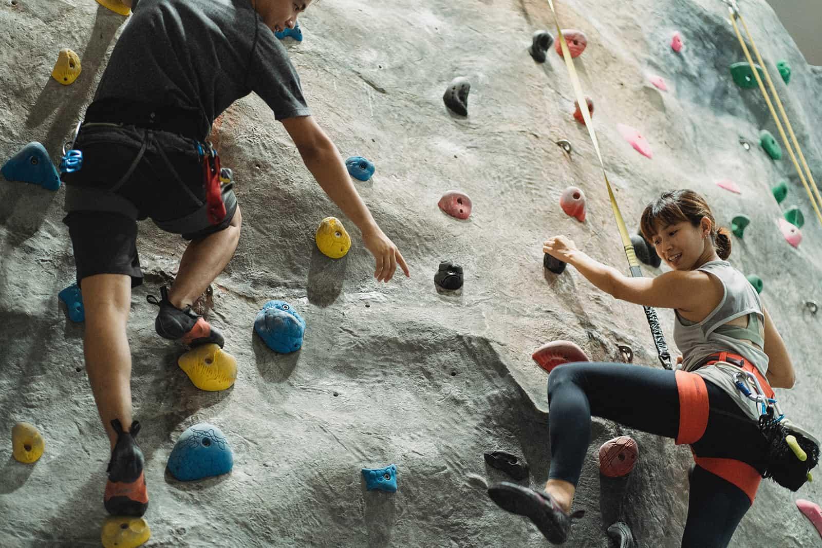 ein Mann und eine Frau trainieren auf einer Kletterwand Zeit miteinander verbringen