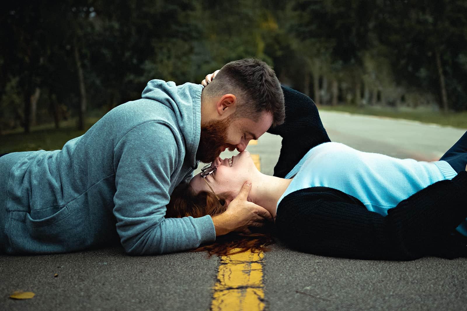 ein Paar, das auf der Asphaltstraße liegt und sich küssen will
