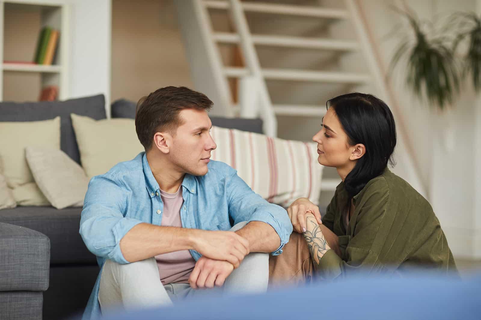 Ein Paar redet aufrichtig miteinander, während es zu Hause auf dem Boden sitzt