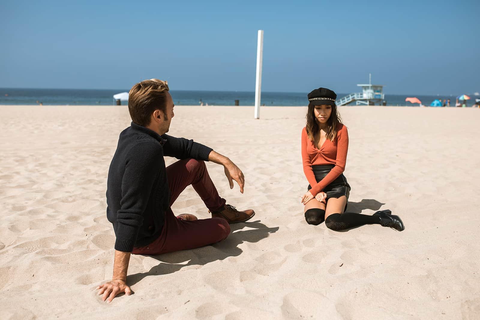 ein Paar, das nach einem Streit schweigend im Sand sitzt