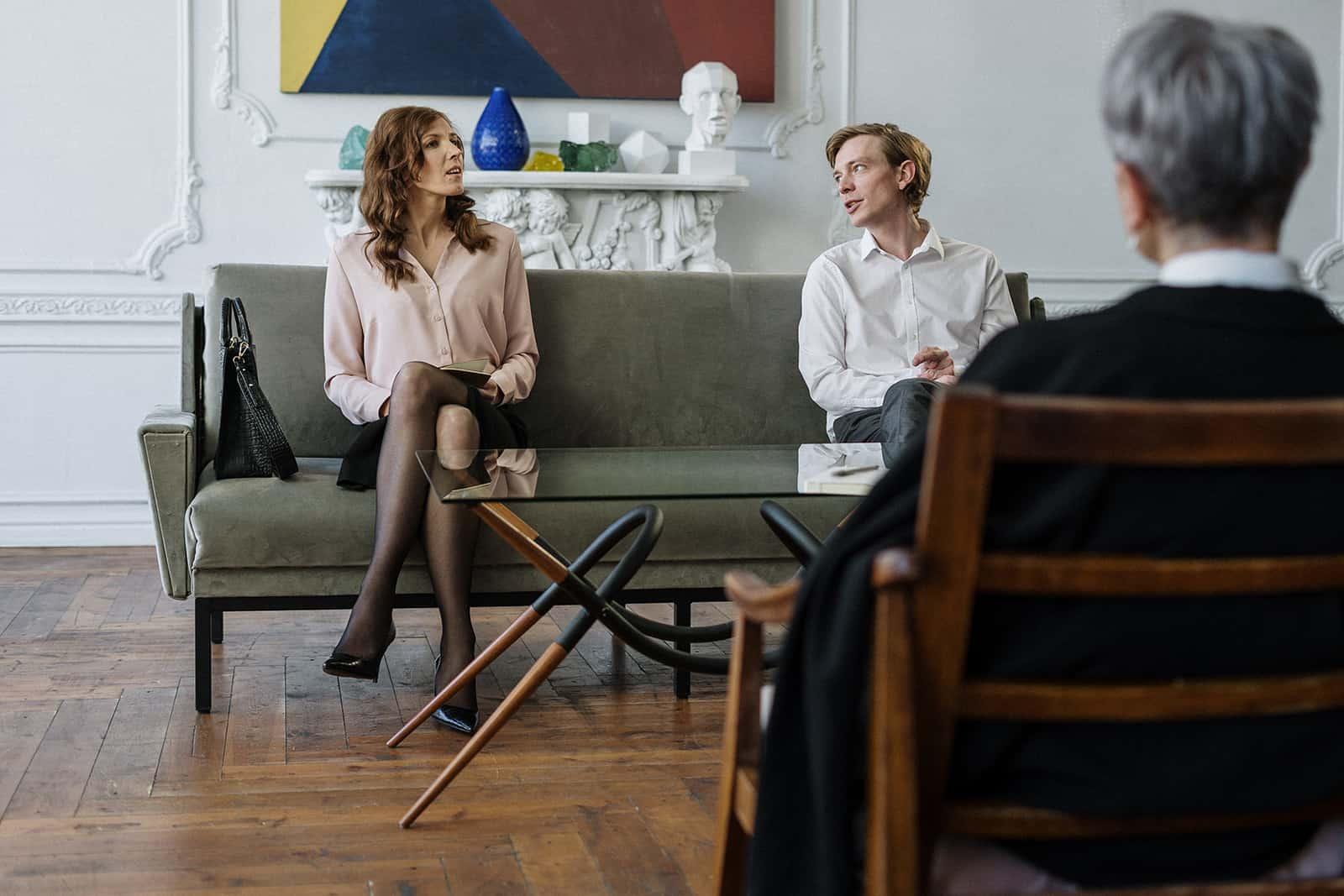 ein Paar, das vor einem Therapeuten sitzt und miteinander spricht