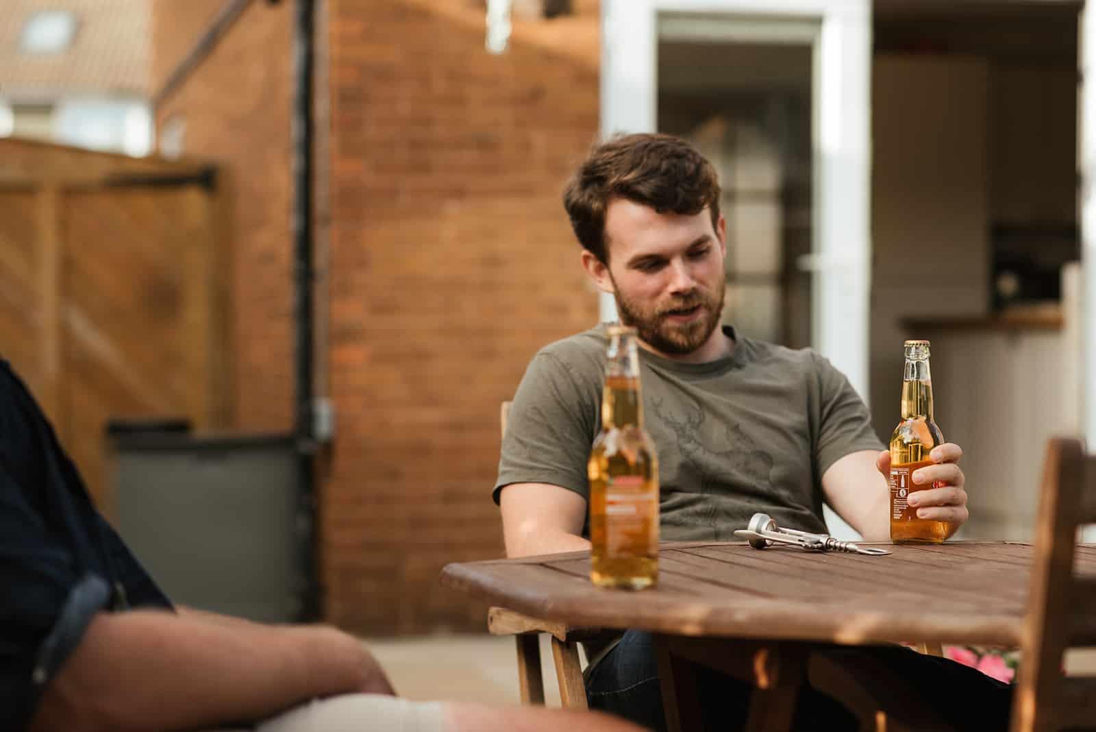 Ein bärtiger Mann, der Bier hält und mit Freunden sitzt