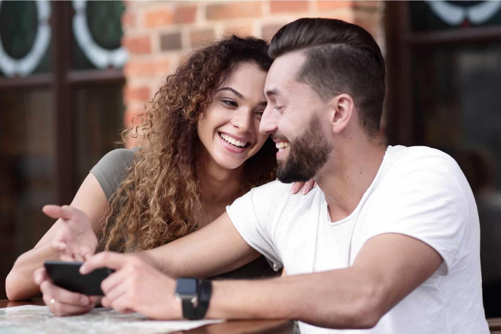 ein glückliches Paar auf der Caféterrasse sitzt und benutzt ein Smartphone