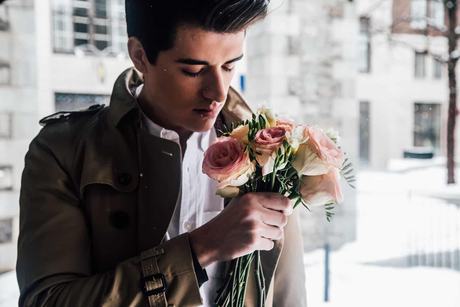 ein hübscher junger Mann, der einen Strauß rosa Rosen hält und daran riecht