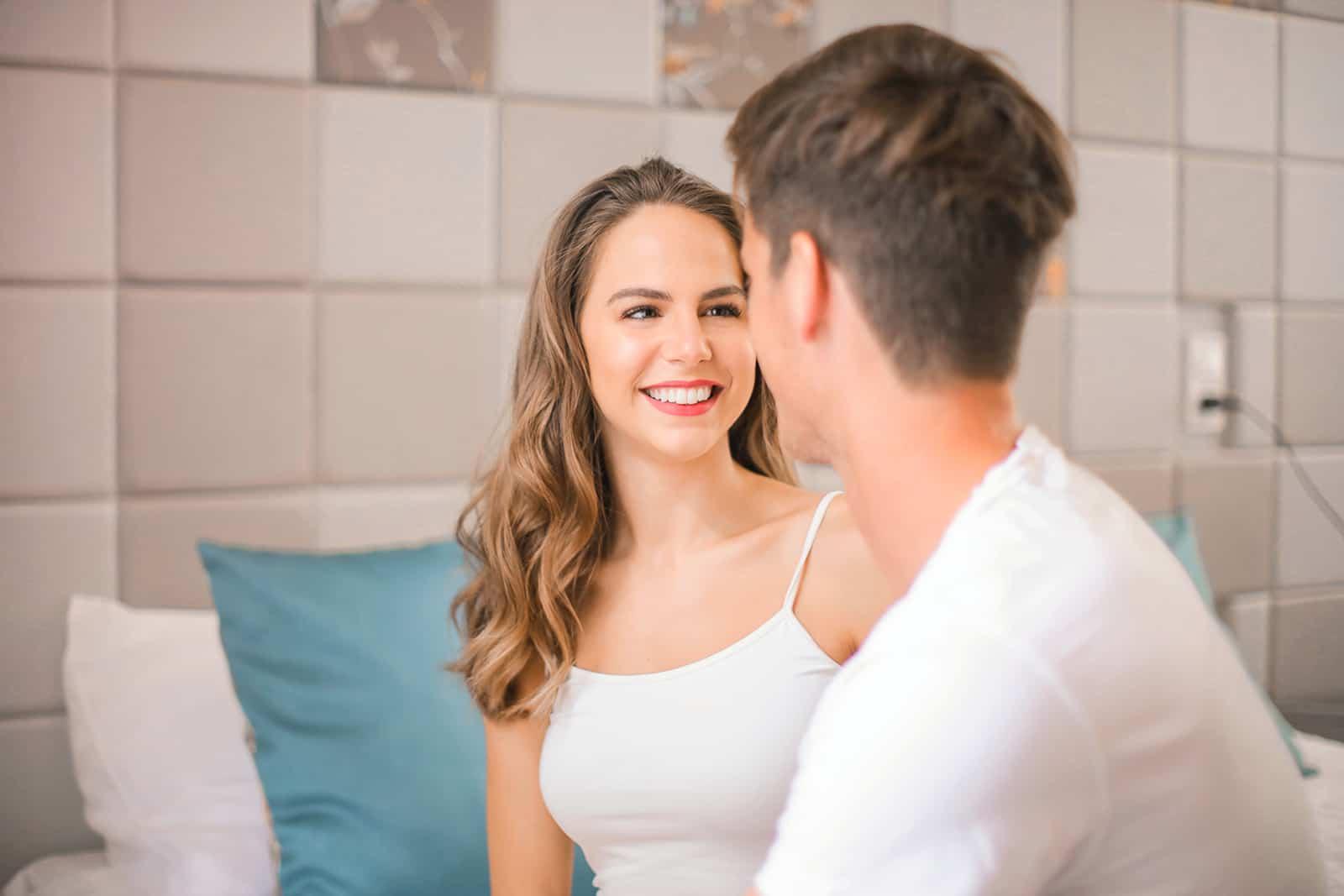 ein lächelndes Mädchen, das einen Mann ansieht, der nahe bei ihr auf dem Bett sitzt