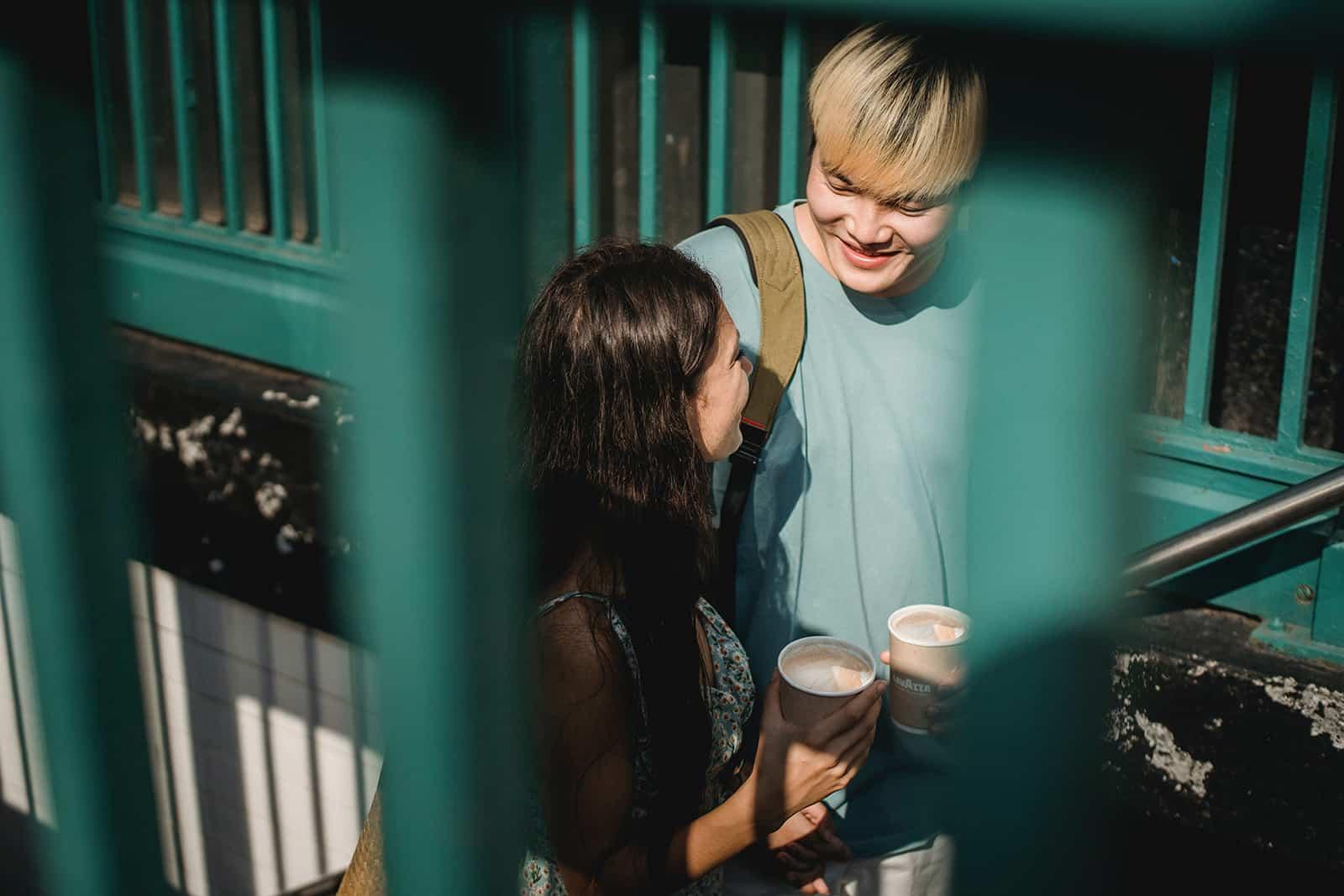 ein lächelndes Paar, das einen Kaffee hält, während es durch Treppen steigt