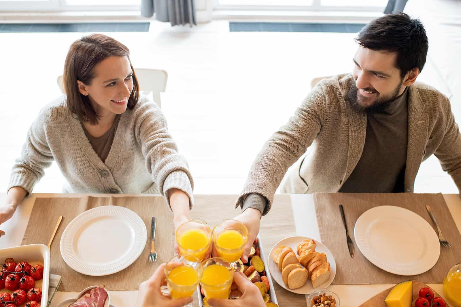 ein lächelndes Paar, das sich beim Anstoßen mit Freunden während des Mittagessens ansieht