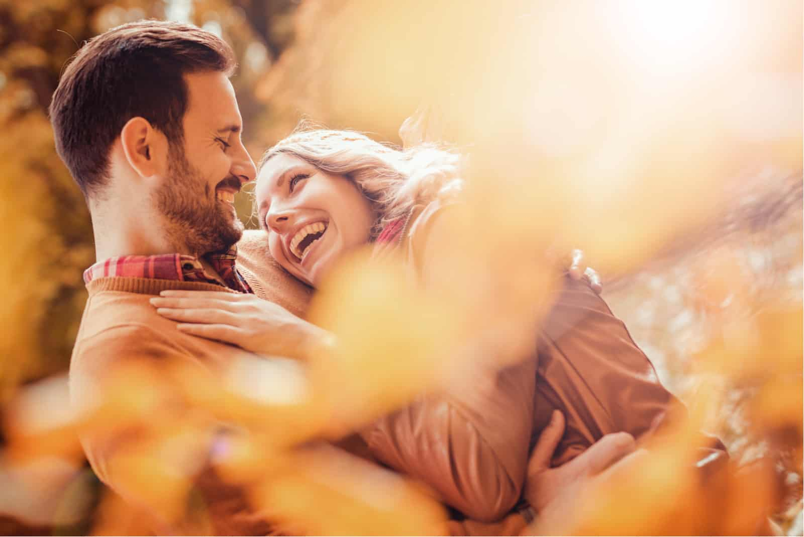 ein lächelndes Paar im Park umarmt sich
