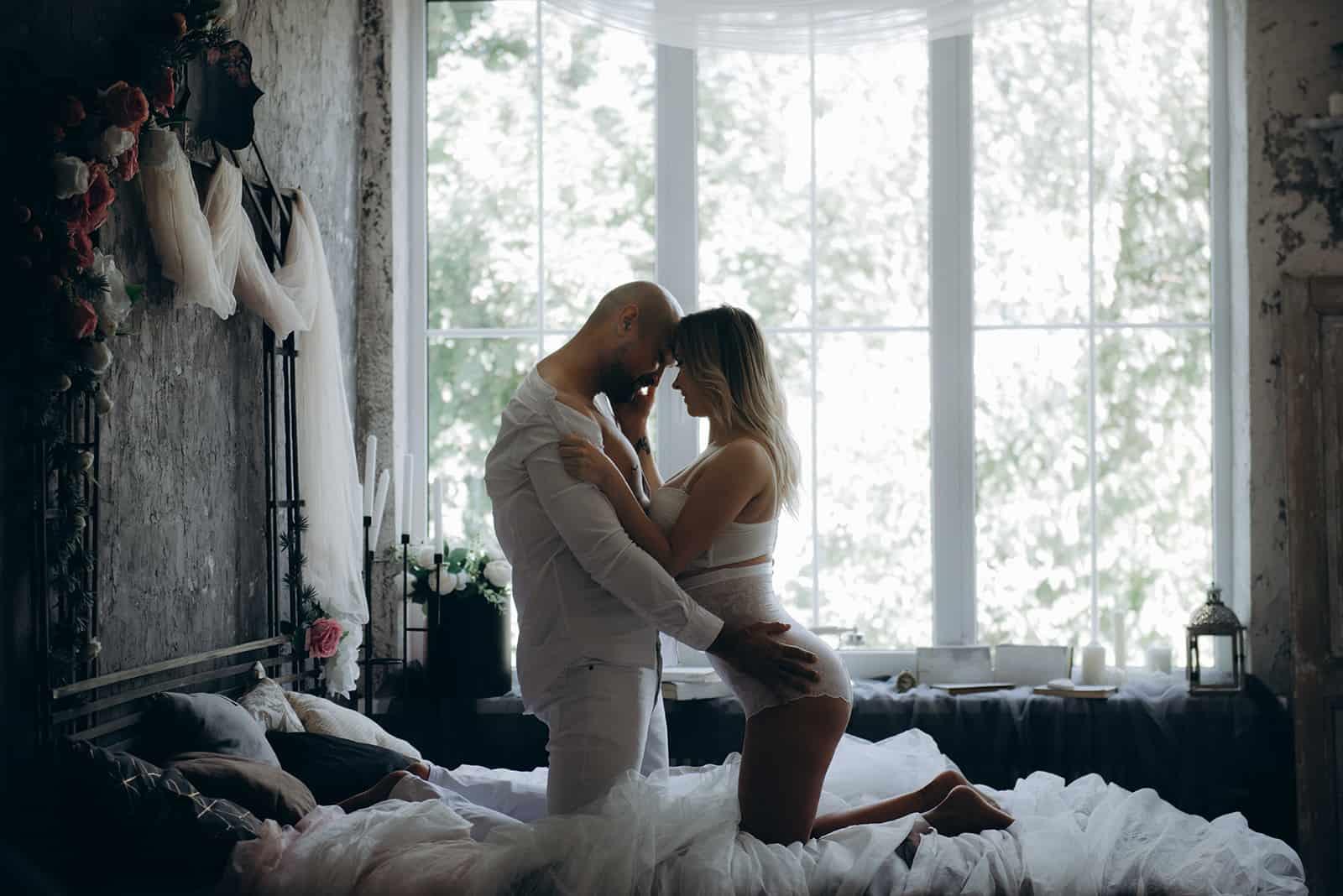Ein liebevolles Paar kuschelt auf dem Bett