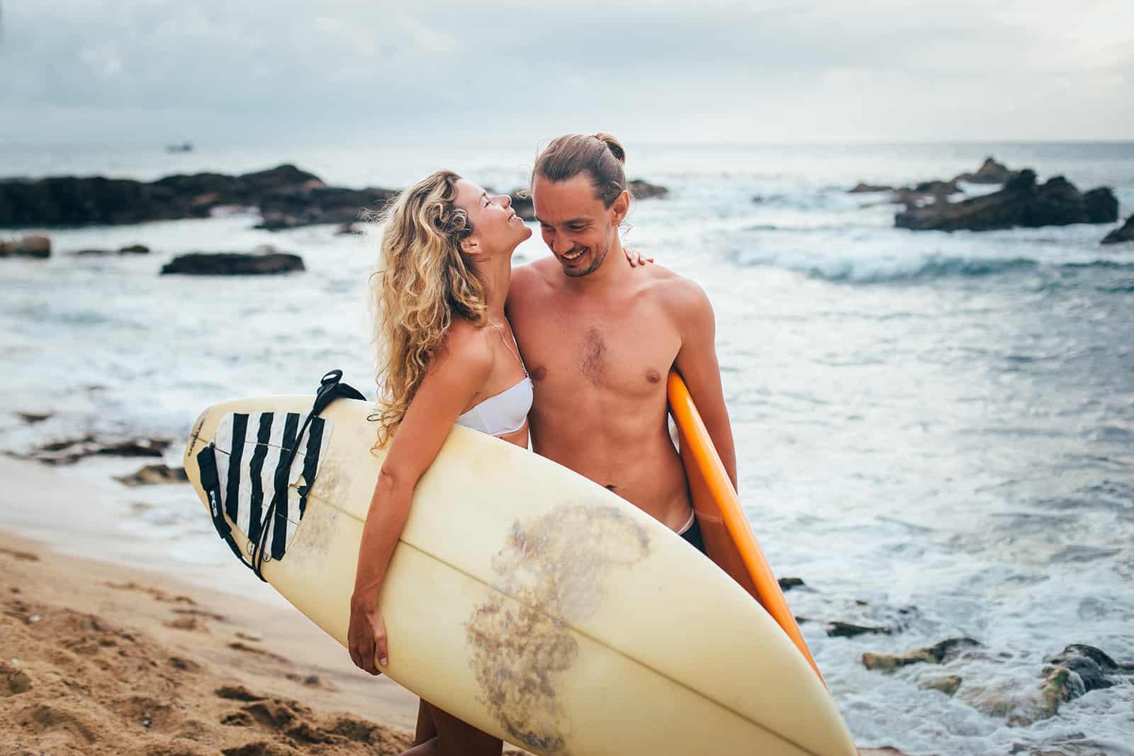 ein liebendes Paar, das Surfbretter hält, die am Strand umarmen
