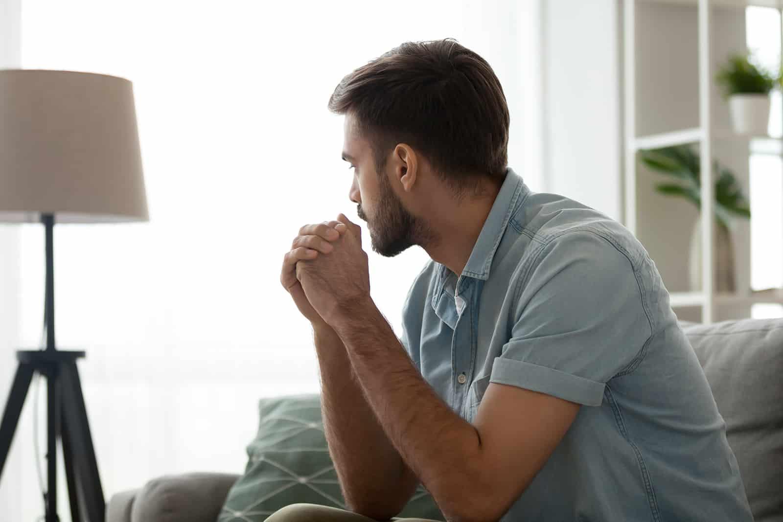 ein nachdenklicher Mann, der auf der Couch sitzt und zur Seite schaut
