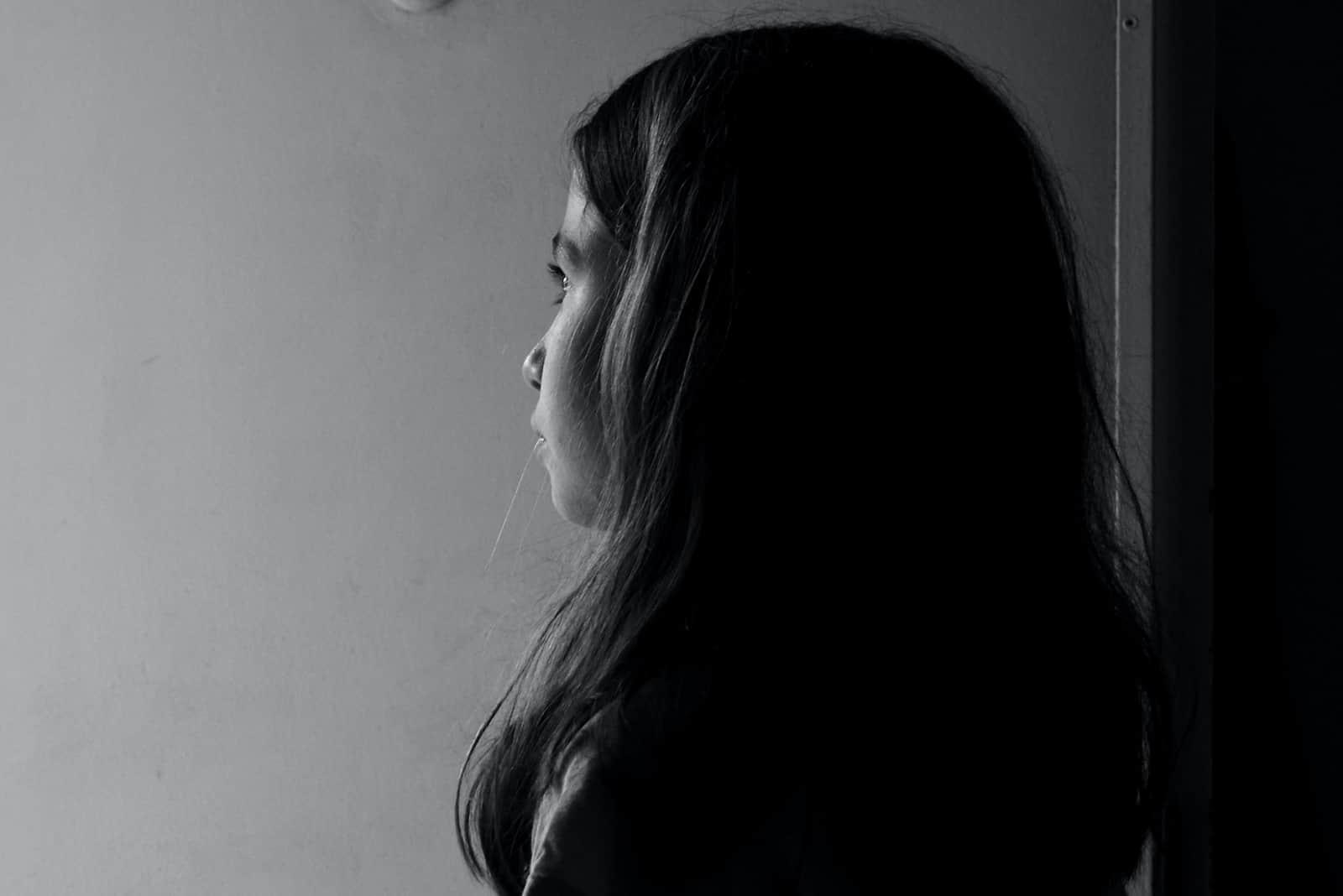 ein nachdenkliches junges Mädchen, das gut an der Tür steht