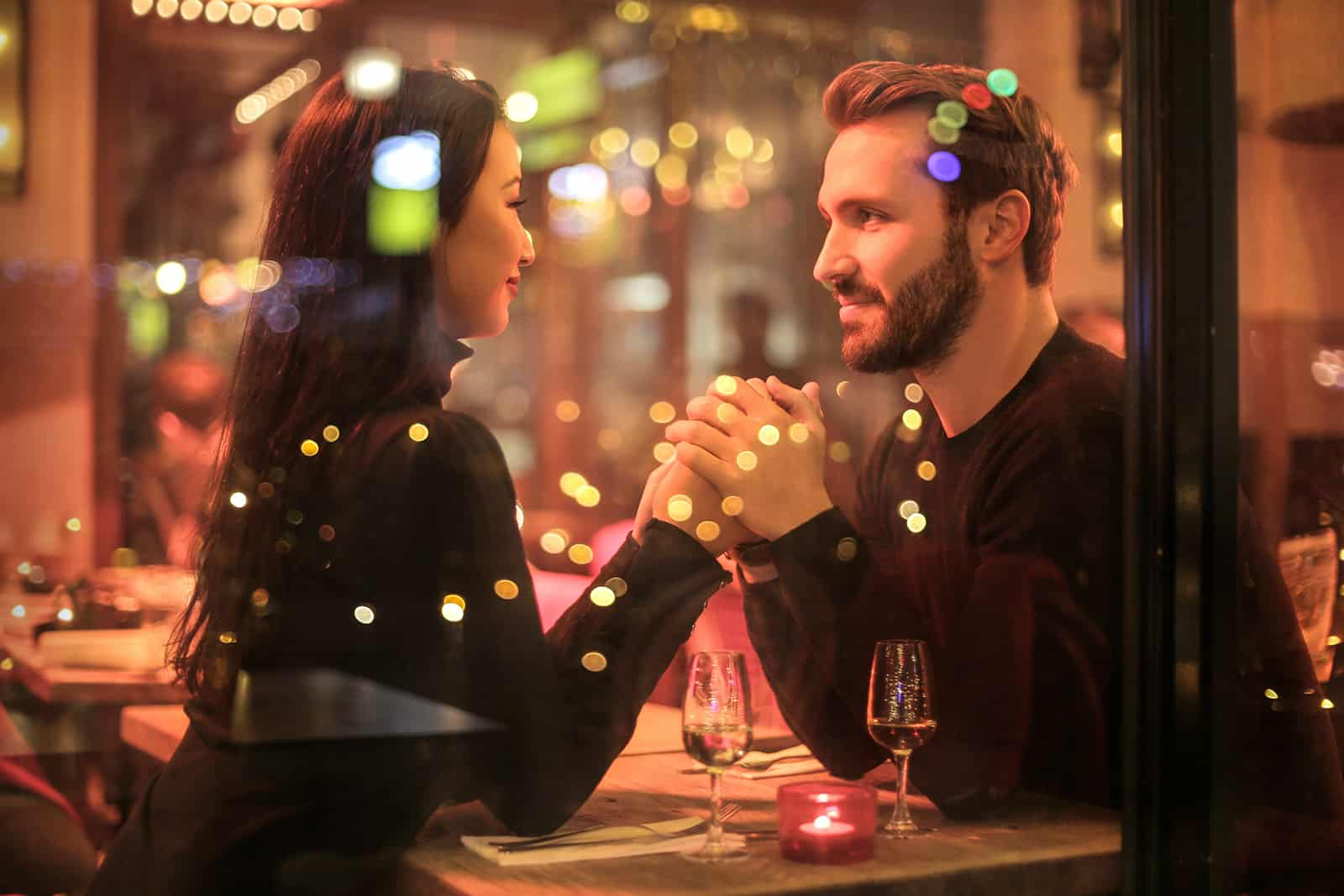 ein Paar Händchen haltend bei einem Date in einem romantischen Restaurant
