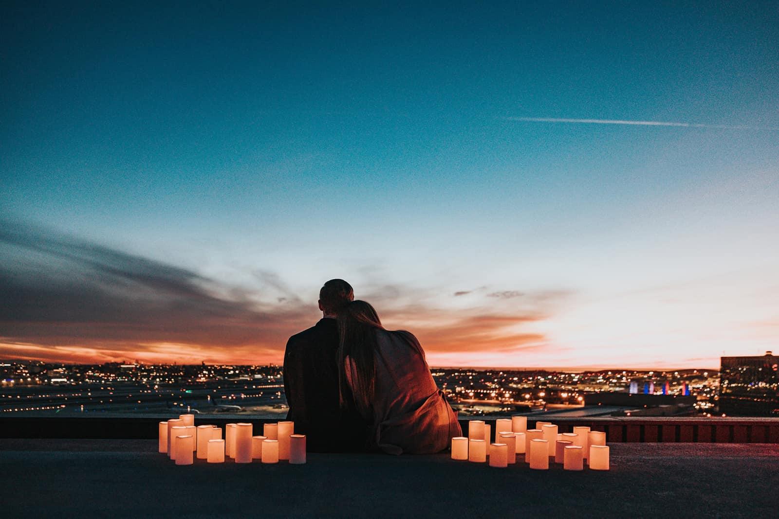 ein Paar sitzt auf dem Beton, umgeben von Kerzen