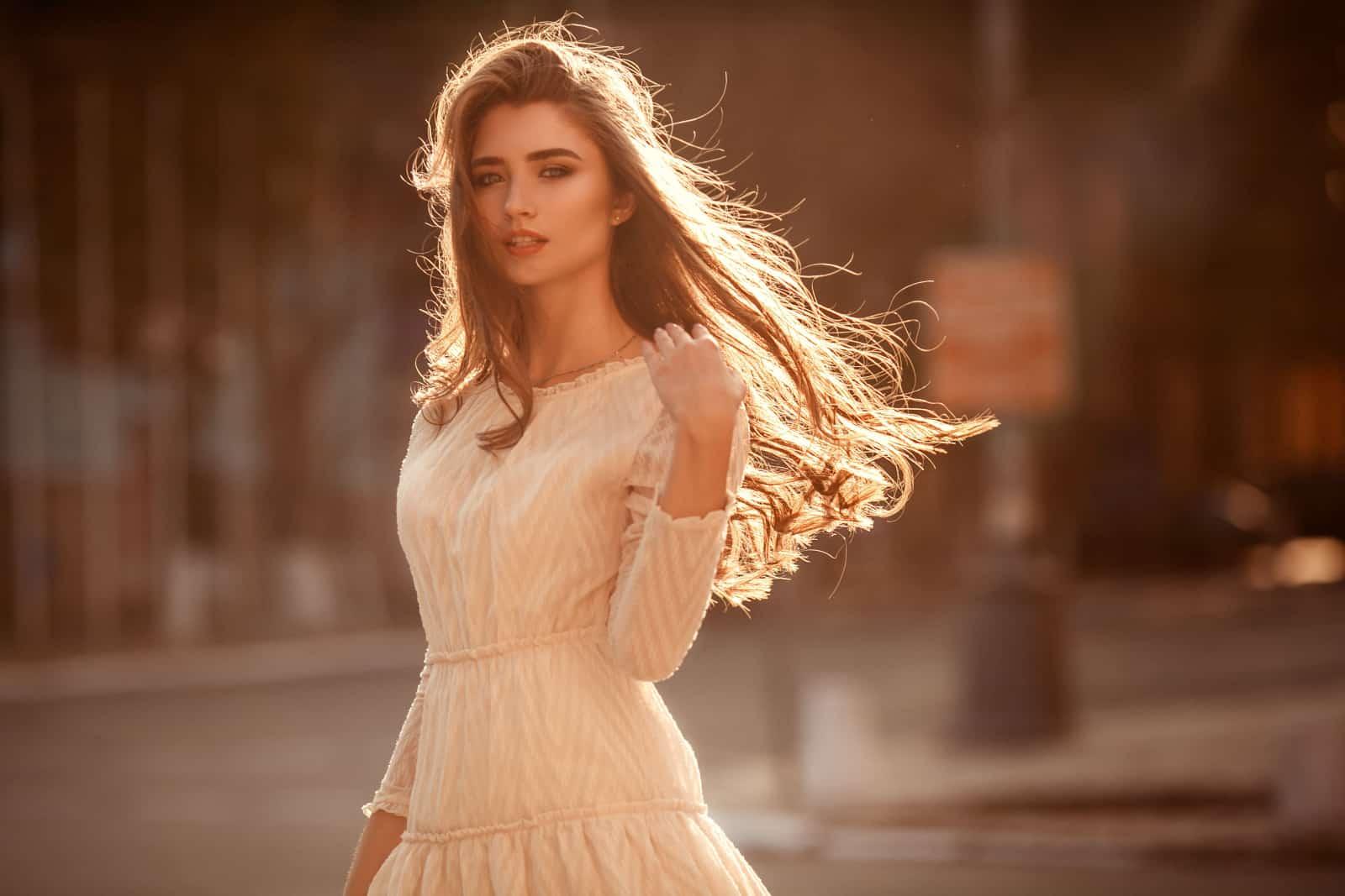 ein schönes junges Mädchen in einem weißen Kleid