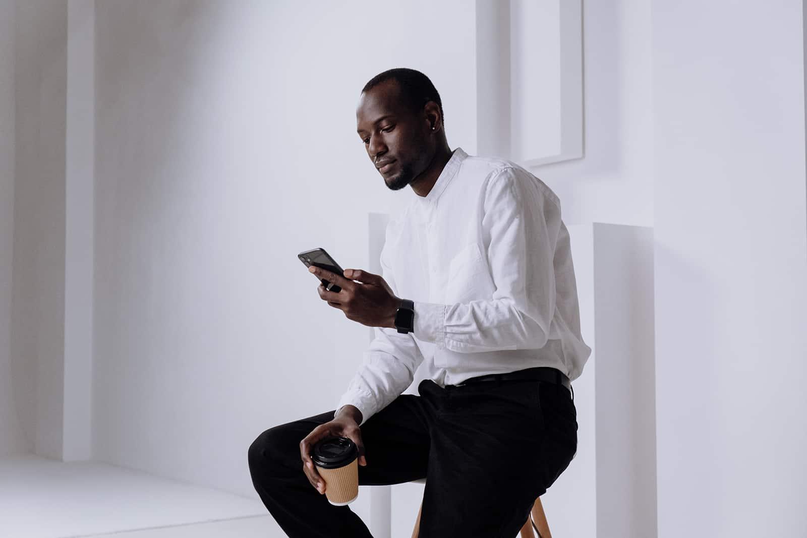 Ein selbstbewusster Mann, der auf seinem Smartphone tippt, während er auf dem Stuhl sitzt