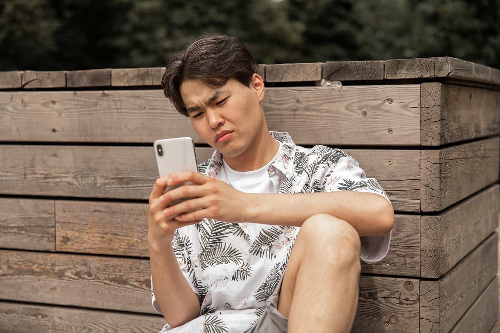 Ein missfallener Mann, der auf sein Smartphone schaut und sich an die Holzwand lehnt