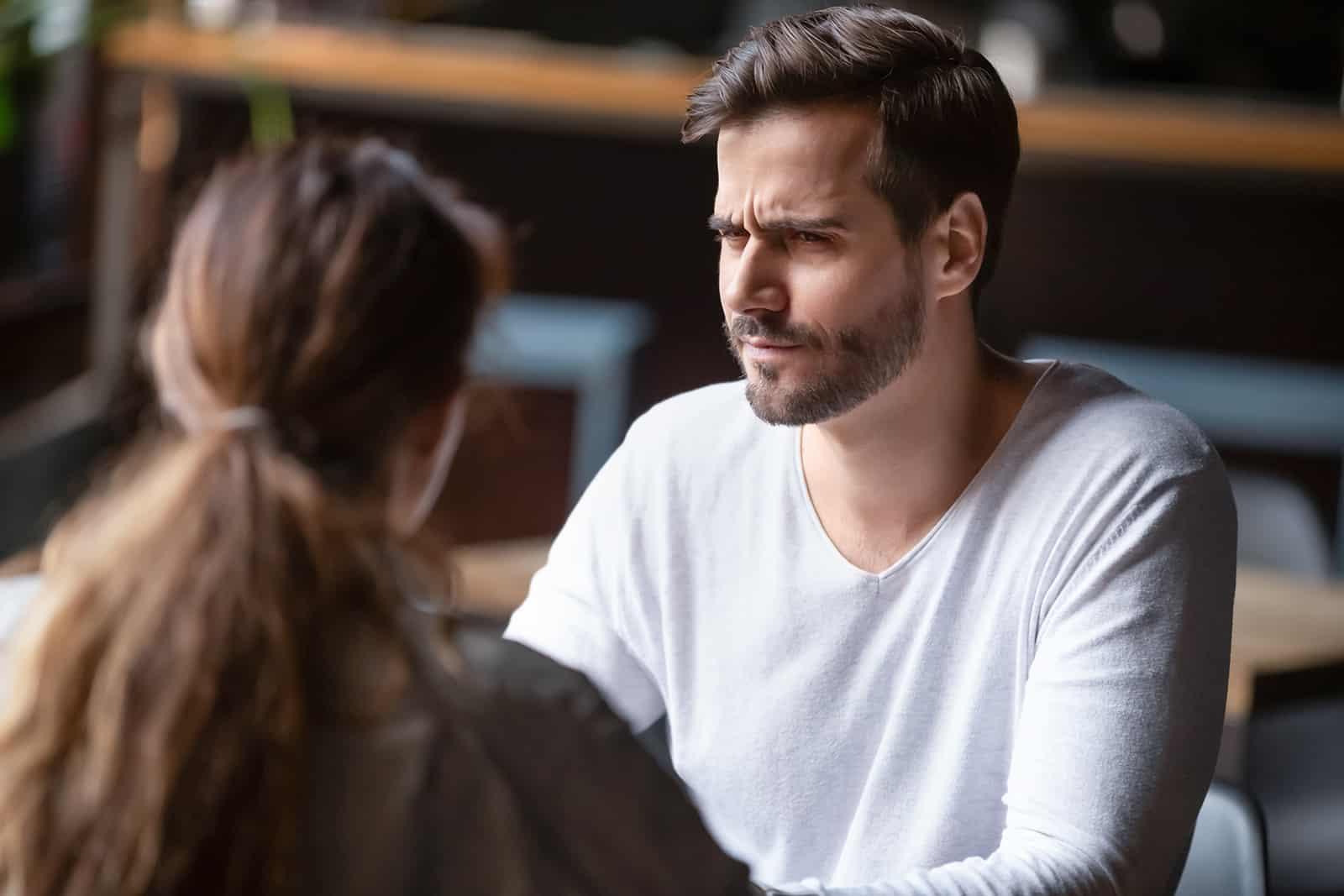 ein verwirrter Mann, der eine Frau ansieht, die mit ihm im Café sitzt