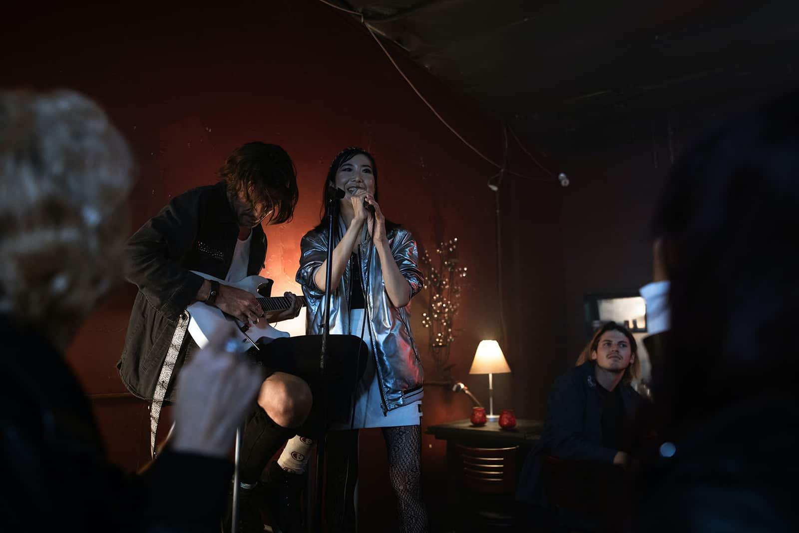 eine Frau, die während der Karaoke-Nacht am Mikrofon singt