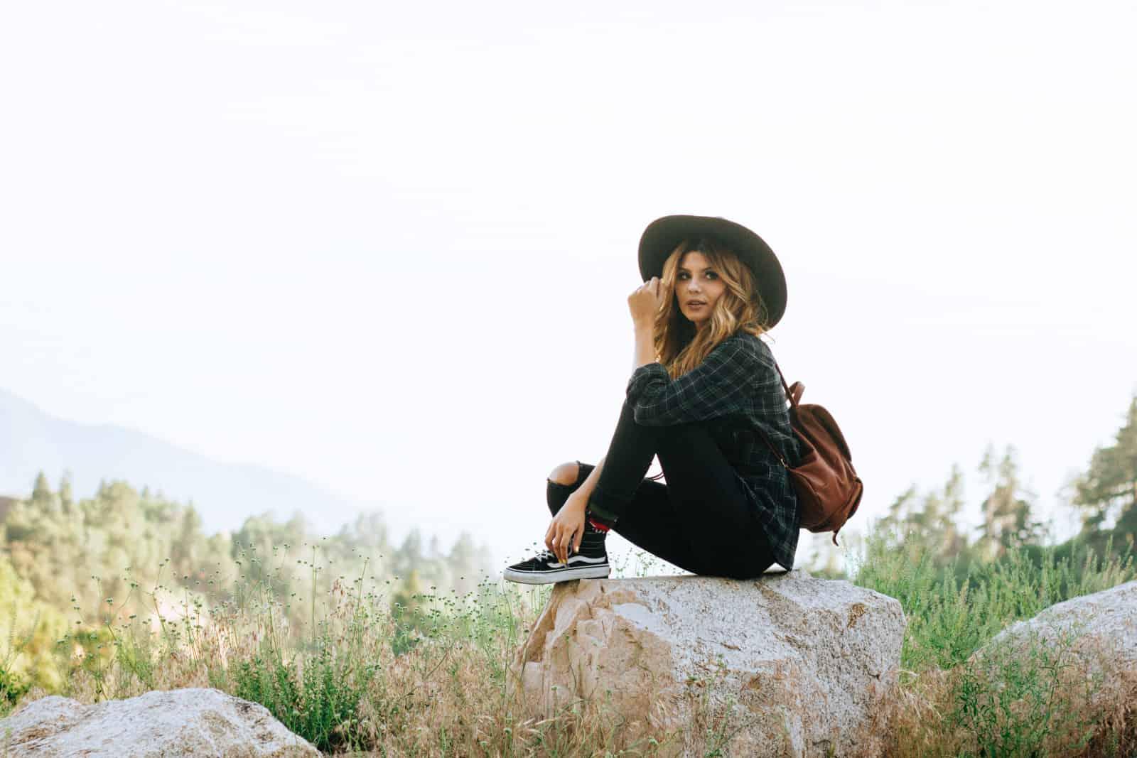 eine Frau, die auf einem Felsen im Wald sitzt
