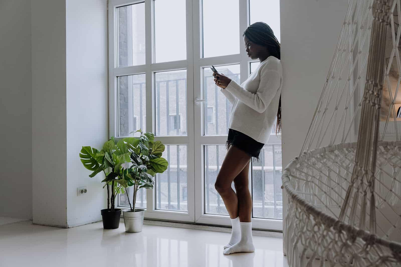 eine Frau, die auf einem Smartphone tippt, das an die Wand in einer Wohnung lehnt