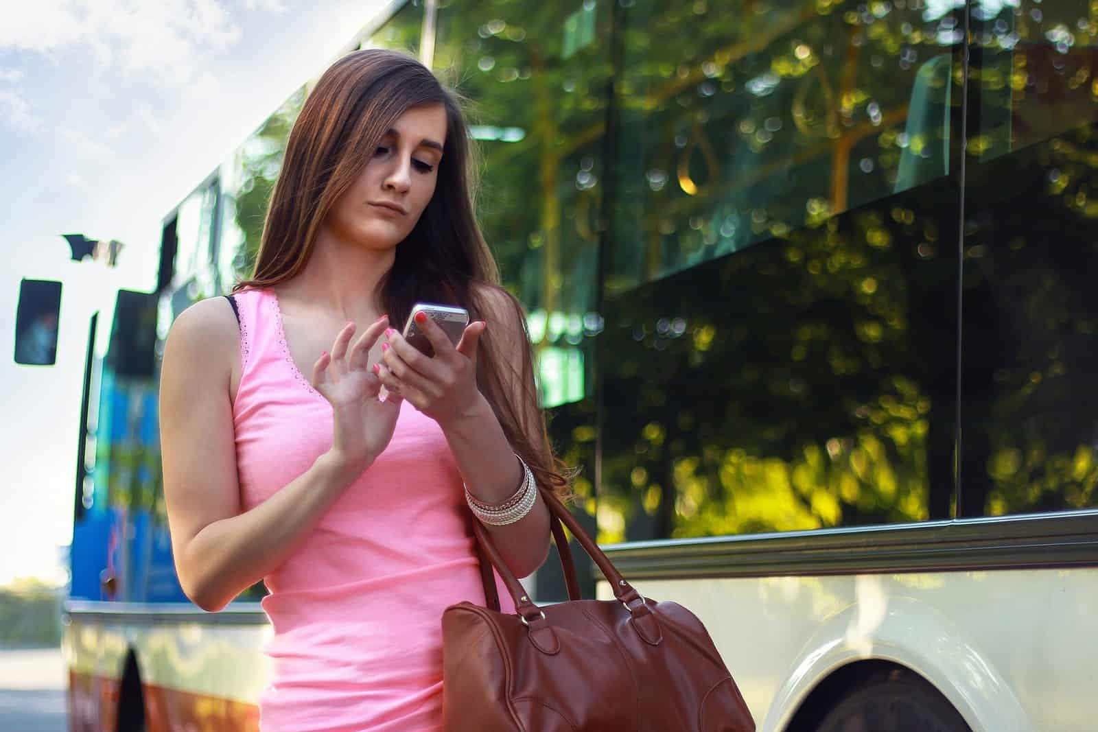 eine Frau, die auf einem Smartphone tippt und gelangweilt aussieht, während sie auf der Straße steht