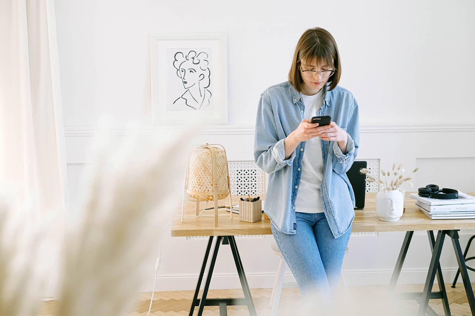 eine Frau, die auf einem Smartphone tippt und sich auf den Schreibtisch lehnt