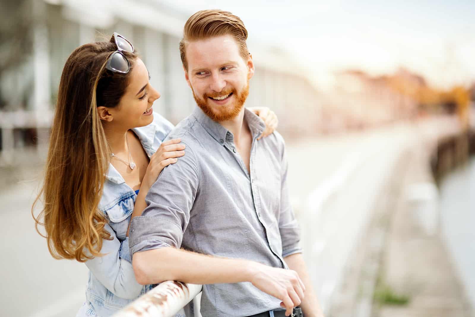 eine Frau, die die Schultern eines Mannes berührt während sie lächeln und sich ansehen
