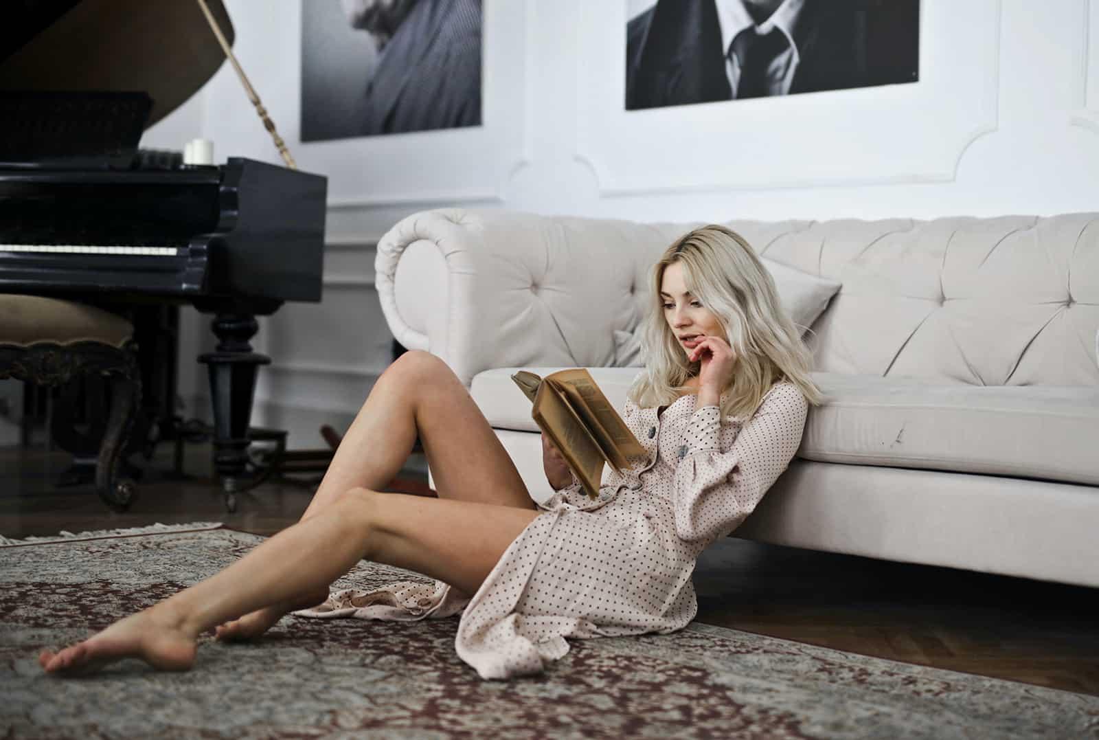 eine Frau, die ein Buch liest, das auf dem Teppich sitzt