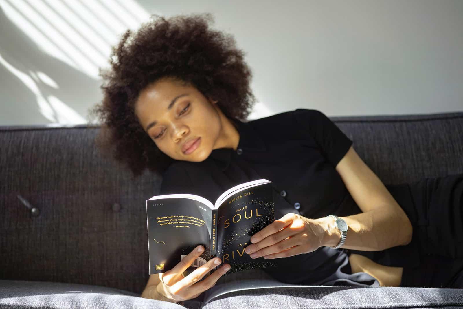 eine Frau, die ein Buch liest, während sie auf der Couch liegt