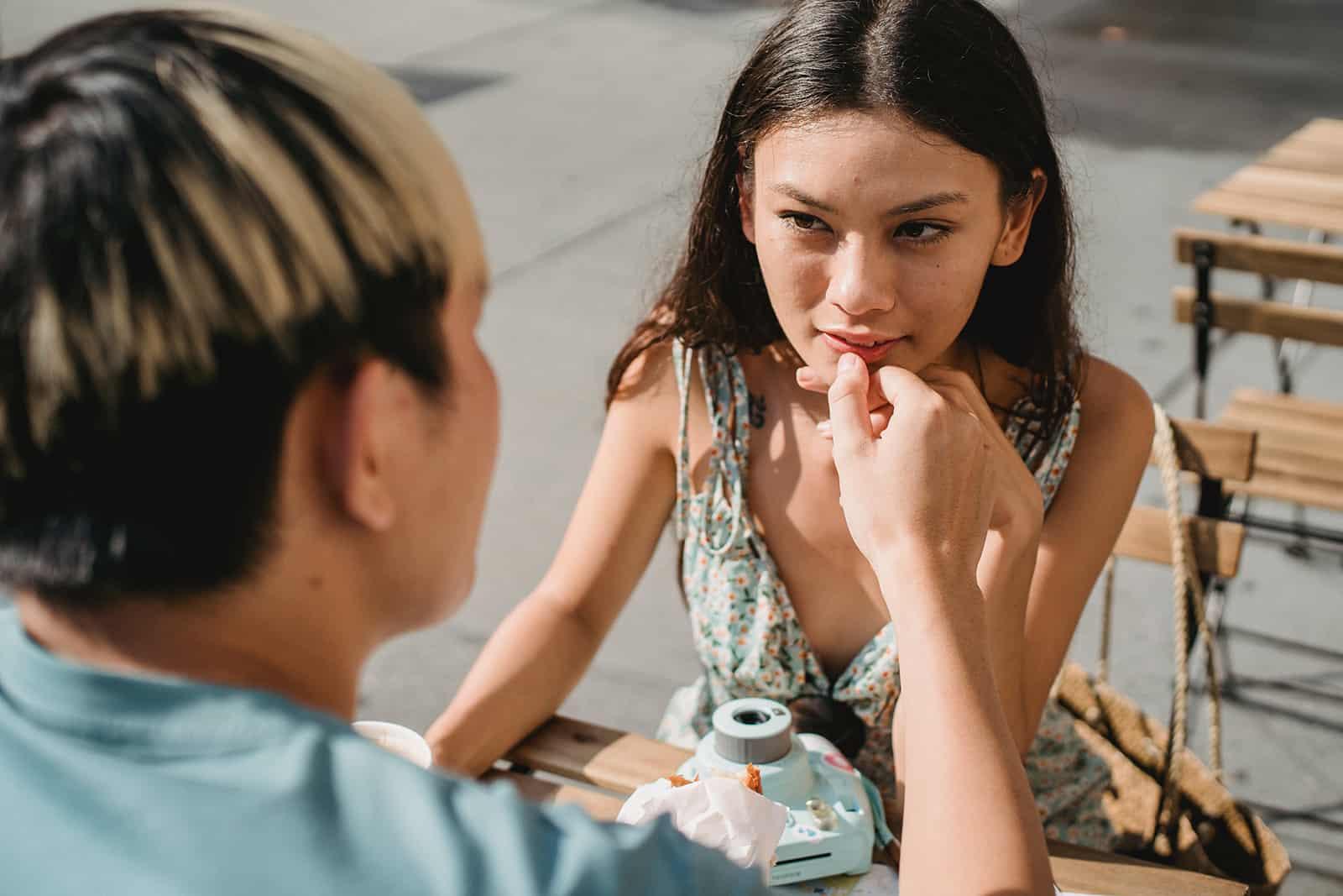 eine Frau, die einen Mann betrachtet, der ihre Lippen berührt, während sie zusammen am Tisch draußen sitzen