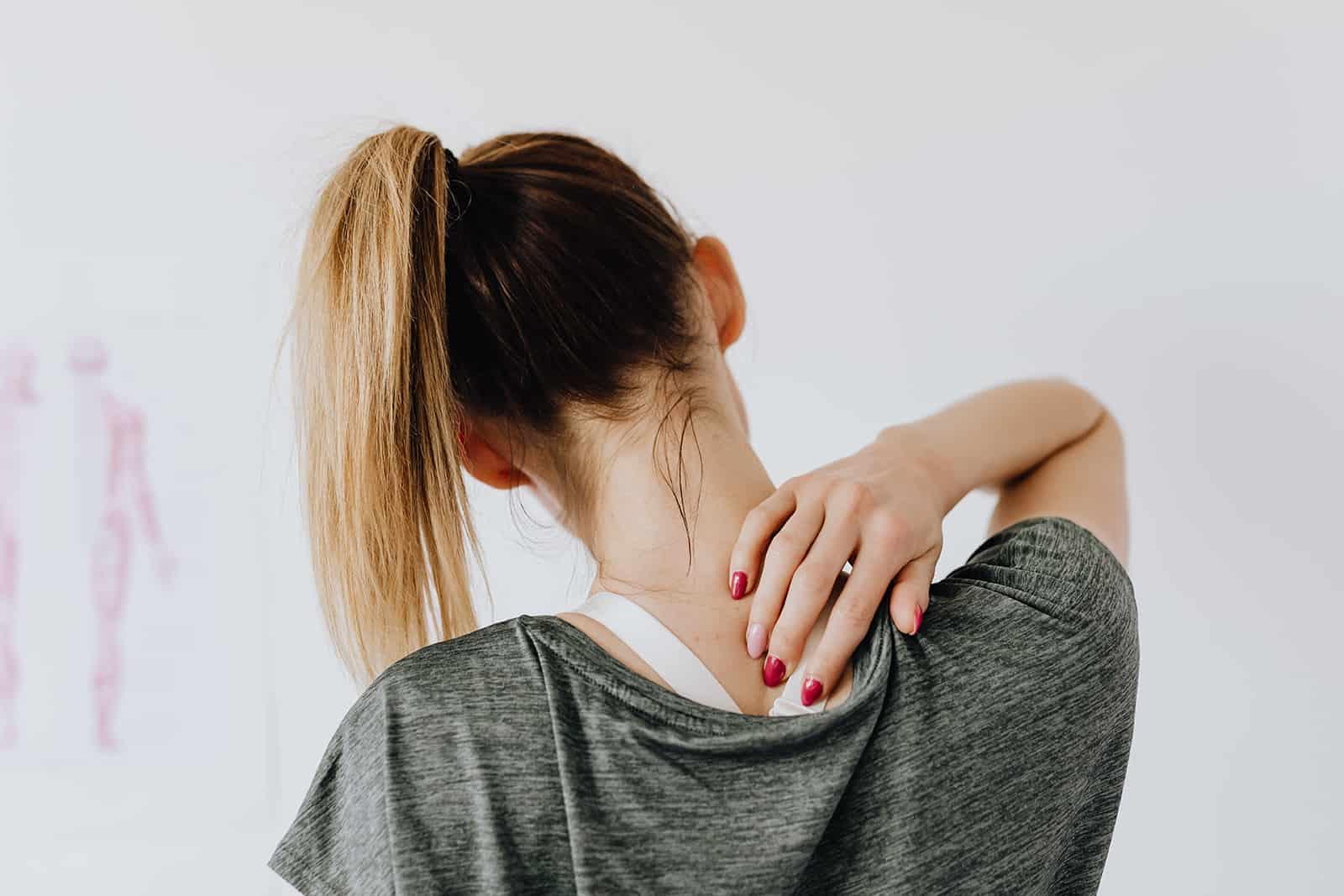 eine Frau, die ihren Schmerzpunkt auf ihrem Rücken berührt