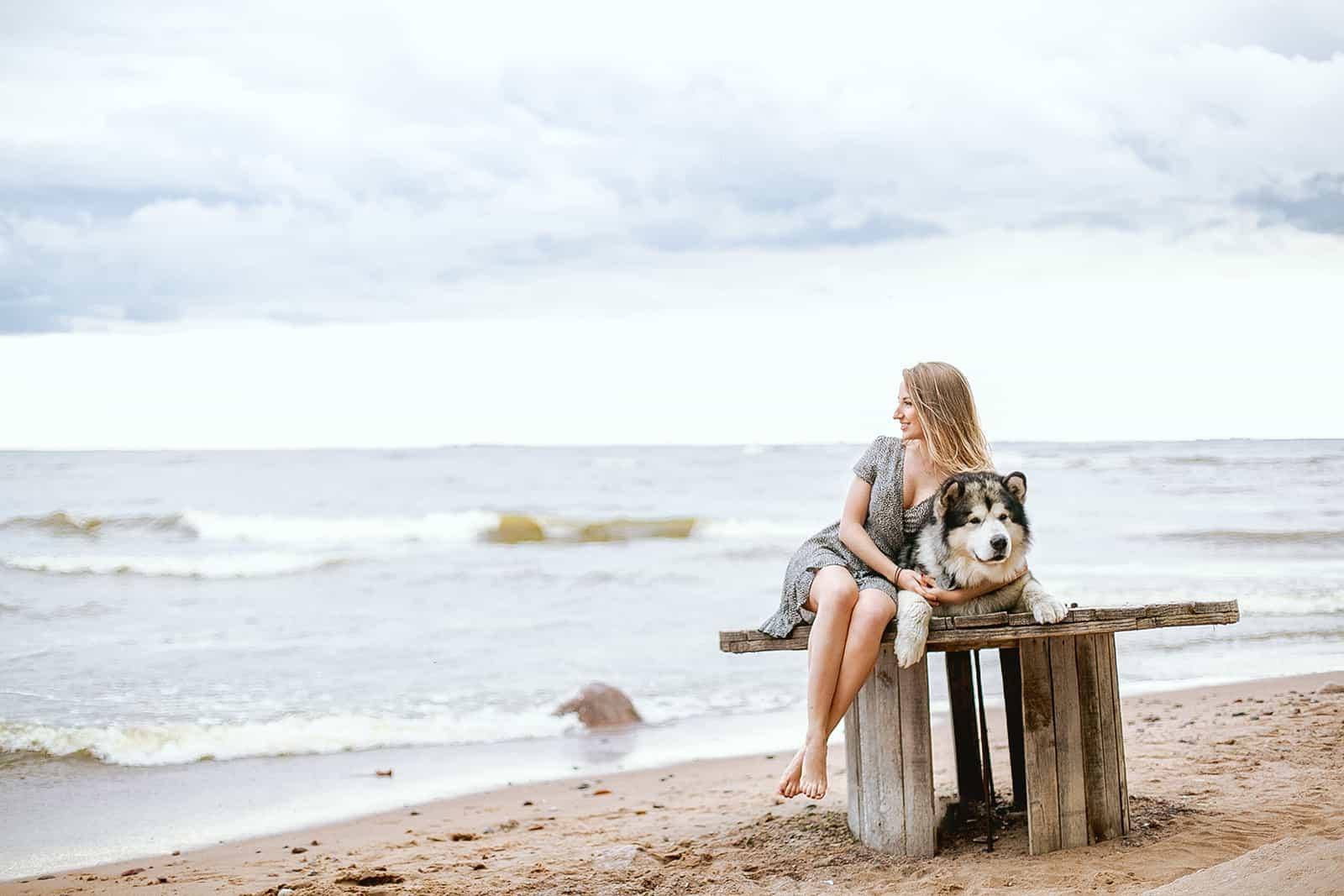 eine Frau, die mit einem Hund auf dem Holztisch am Strand sitzt