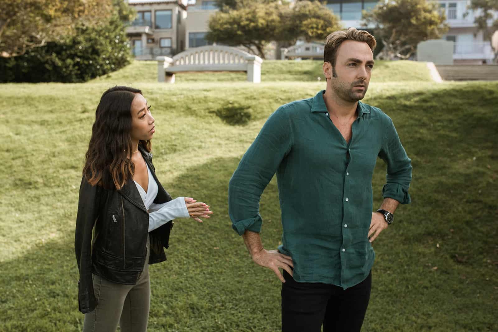 eine Frau, die mit einem eifersüchtigen Mann spricht, der zusammen im Park steht