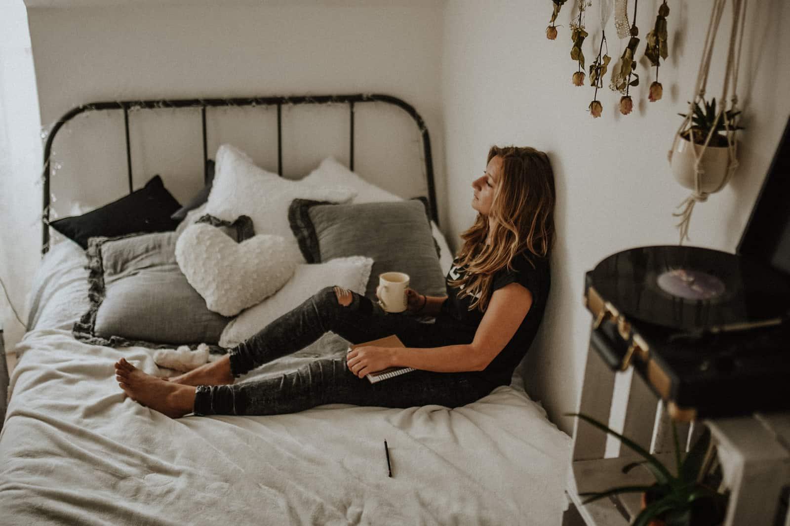eine Frau, die sich auf dem Bett entspannt und Kaffee trinkt