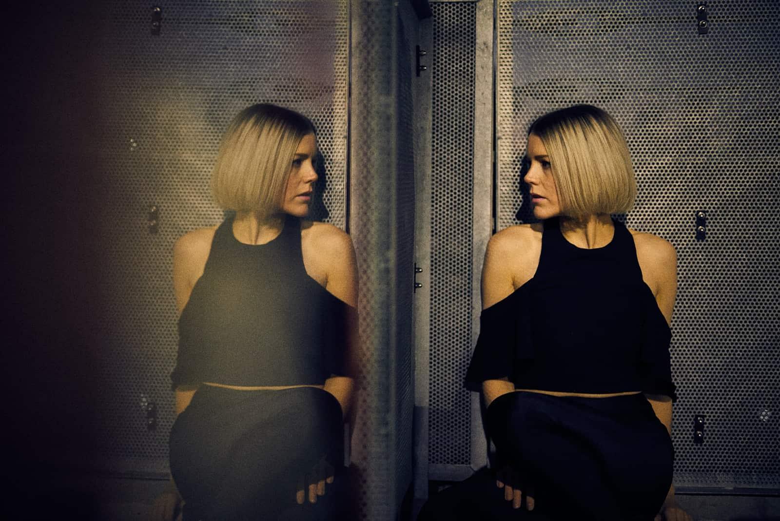 eine Frau, die sich nachdenklich im Spiegel ansieht
