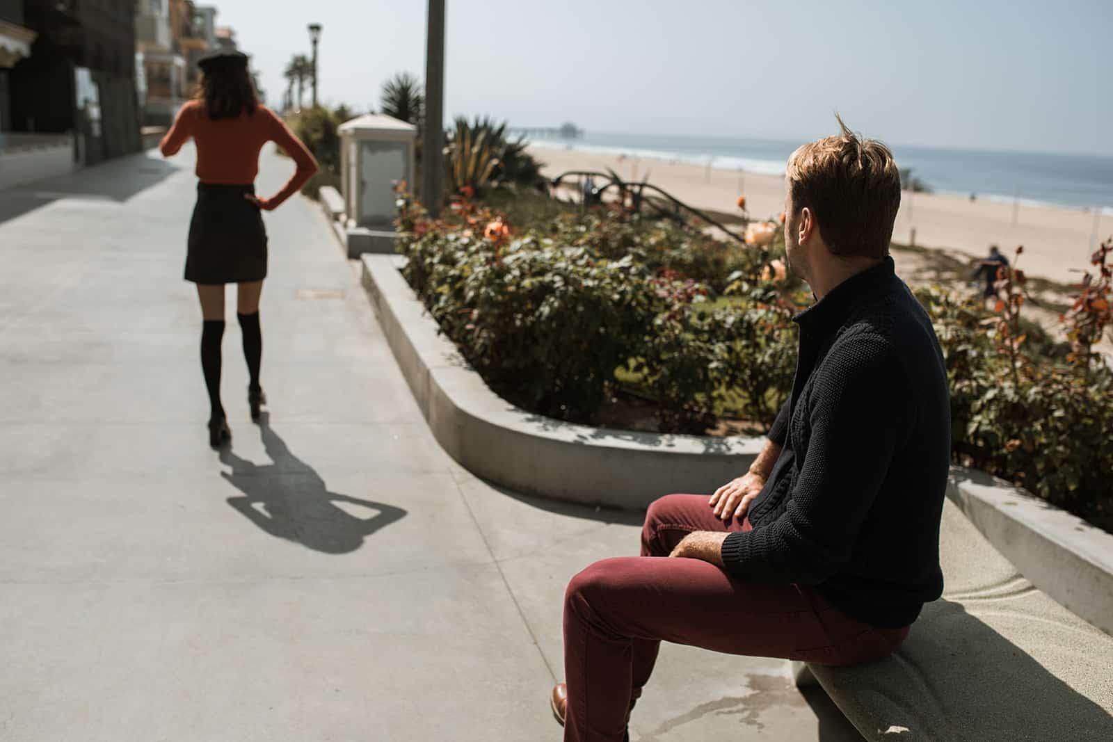 eine Frau, die von einem Mann geht, der auf einer Betonbank sitzt