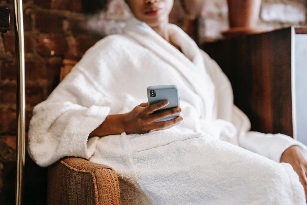 eine Frau im Bademantel, die eine Nachricht auf dem Smartphone tippt, während sie im Sessel sitzt