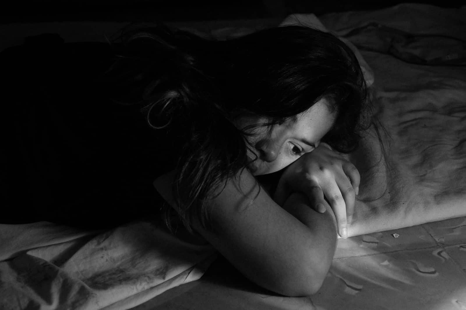 eine Frau, die im Bett liegt und traurig aussieht