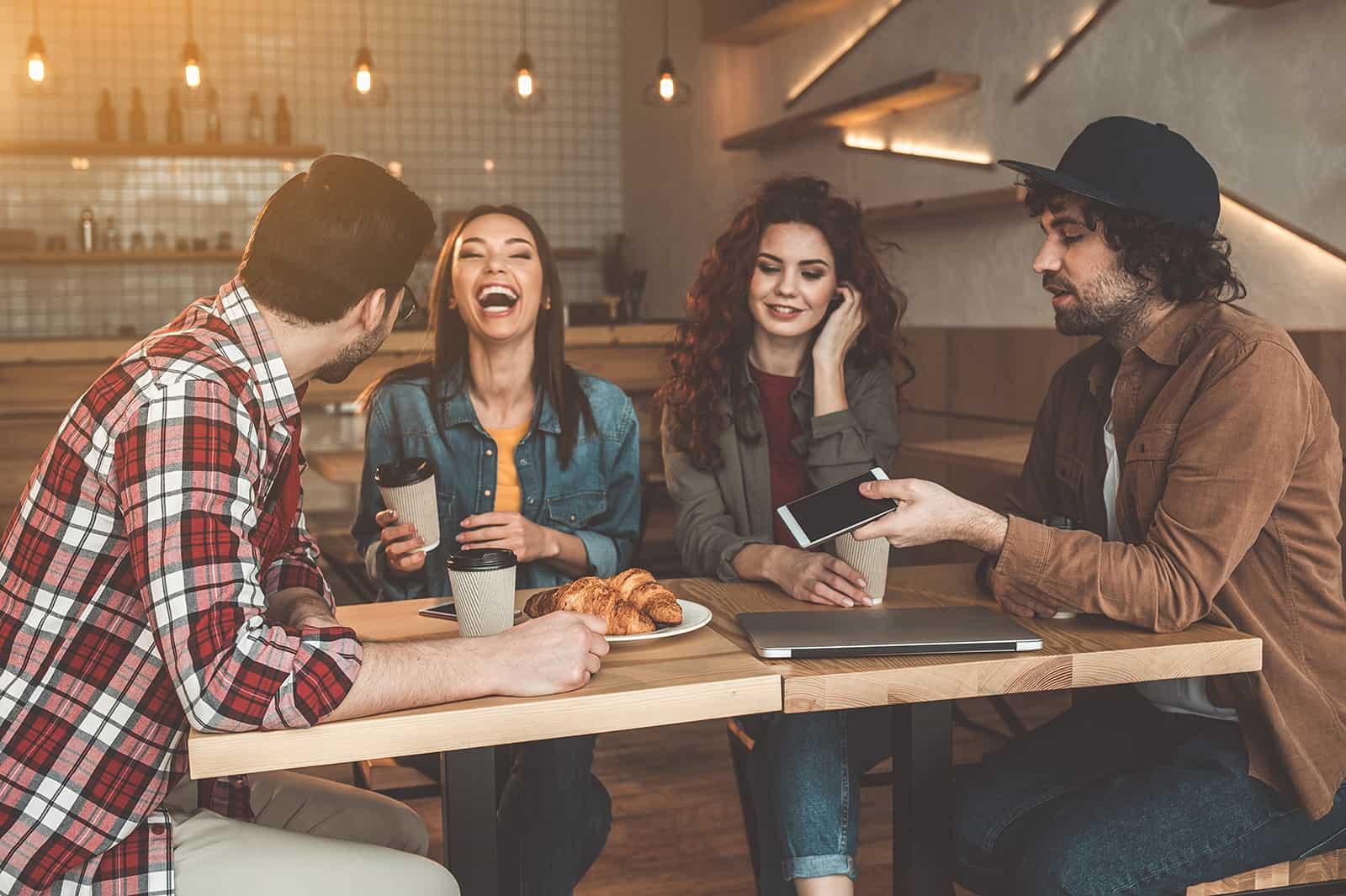 eine Frau lacht, während sie mit Freunden im Café sitzt