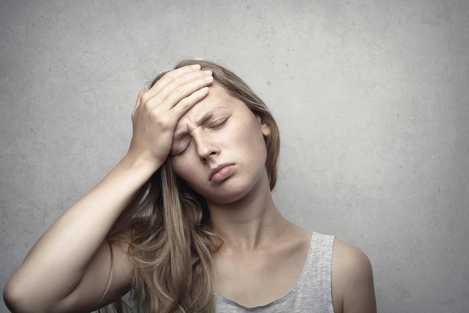 eine Frau mit Migräne die Stirn mit einer Hand berühren